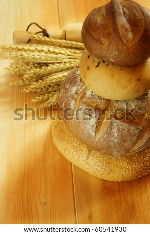 Assorted bread on wooden table with raw wheat and baking roller background
