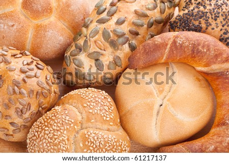 Assorted breads on a wooden plate - stock photo