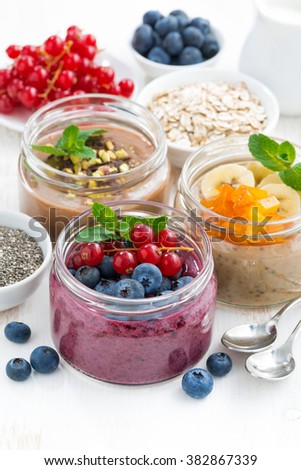 assorted breakfast of chia seeds and fruits in jars on white table, vertical, closeup