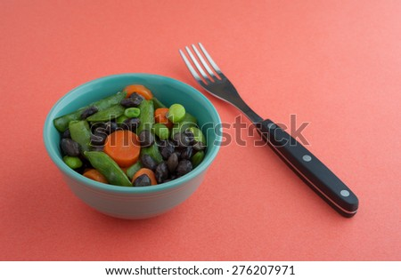 Assorted buttered cooked vegetables in a small bowl with a fork to the side on an orange background illuminated by natural light. - stock photo