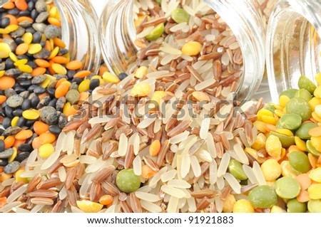 Assorted Cereals Spilling Out of Glass Jars - stock photo