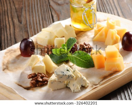 Assorted cheese on a wooden board with honey - stock photo