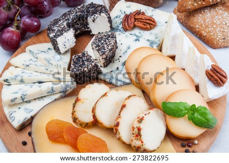 Assorted cheese on wooden board - stock photo