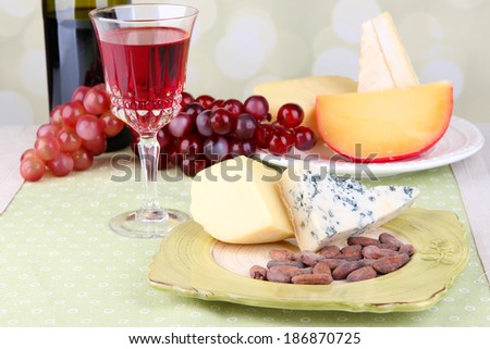 Assorted cheese plate , grape and wine glass on table, on light background