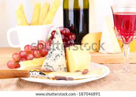 Assorted cheese plate , grape and wine glass on table, on light background - stock photo