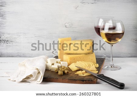 Assorted cheese with olives on board and glasses of red and white wine on rustic wooden background.  - stock photo