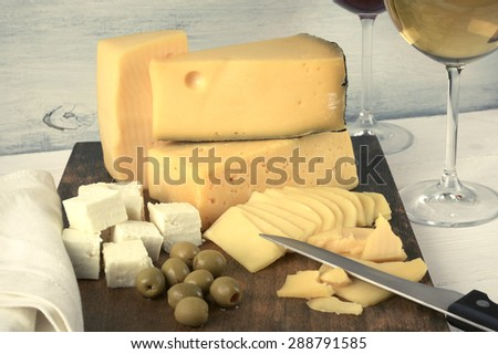 Assorted cheese with olives on board and glasses of red and white wine on rustic wooden background. Toned image. - stock photo