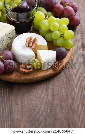 assorted cheeses and fresh grapes on the board and wooden background, vertical, top view - stock photo