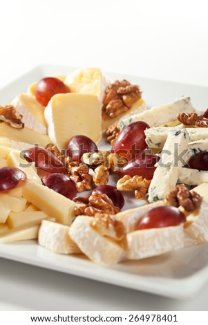 Assorted Cheeses with Grapes and Nuts on Platter - stock photo