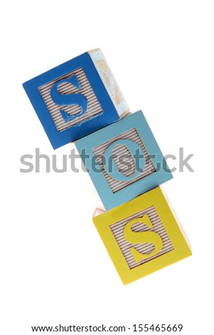 Assorted children's toy letter building blocks against a white background/Children's alphabet blocks spelling the words SOS - stock photo