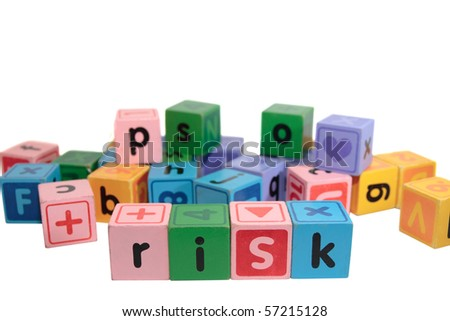 assorted children toy letter building blocks against a white background that spell  risk - stock photo