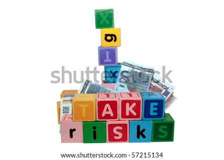 assorted children toy letter building blocks against a white background that spell take risks - stock photo