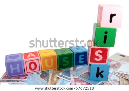 assorted childrens toy letter building blocks against a white background on money that spell house risk