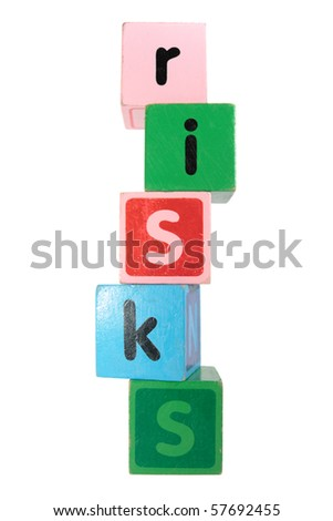 assorted childrens toy letter building blocks against a white background that spell risks - stock photo