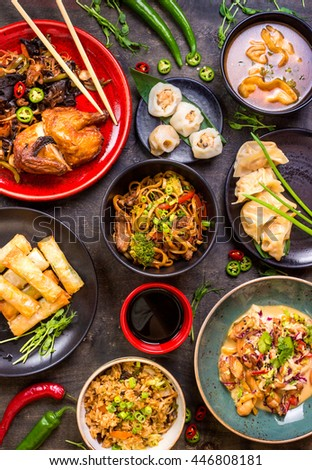 Assorted Chinese food set. Chinese noodles, fried rice, dumplings, peking duck, dim sum, spring rolls. Famous Chinese cuisine dishes on table. Top view. Chinese restaurant concept. Asian style banquet - stock photo