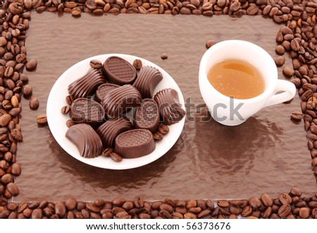 Assorted chocolate candies and cup of tea on brown background