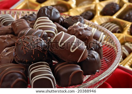 Assorted chocolate candies on crystal serving plate with boxed candy in background.  Macro with shallow dof - stock photo