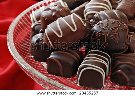 Assorted chocolate candies on crystal serving plate with red background.  Macro with shallow dof. - stock photo