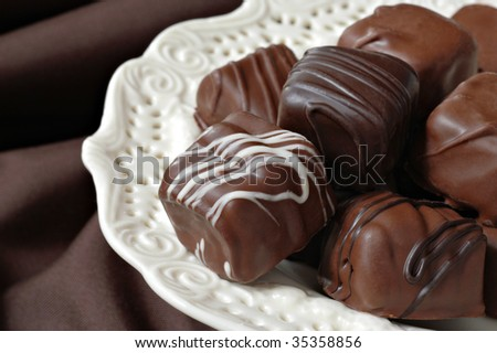 Assorted chocolate candies on elegant porcelain serving plate with brown background.  Macro with shallow dof. - stock photo