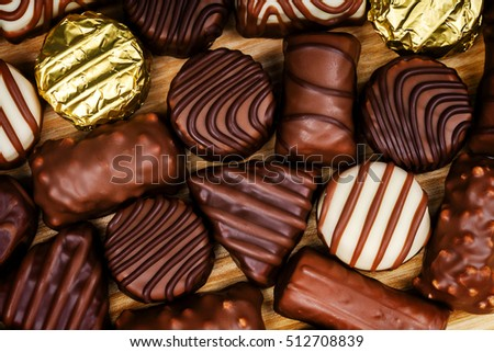 Assorted chocolate candies on wooden table