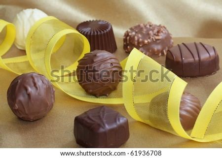 Assorted chocolate pieces with yellow ribbon as decoration - stock photo