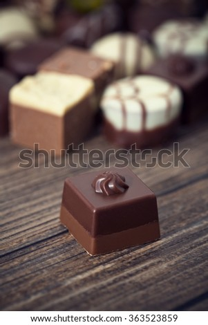 Assorted chocolate pralines on a wooden background. Romantic style