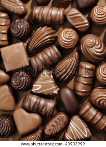 Assorted Chocolate pralines on brown background - stock photo