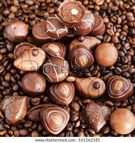 Assorted chocolate pralines on coffee beans background, top view - stock photo