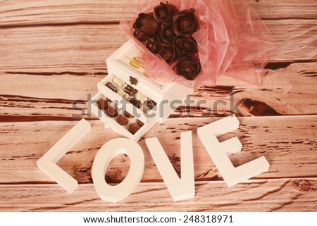 Assorted chocolate pralines on wooden background - stock photo