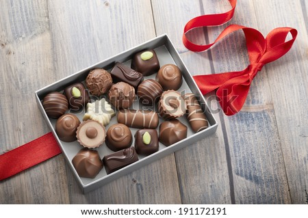 assorted chocolates confectionery in their gift box with red bow - stock photo