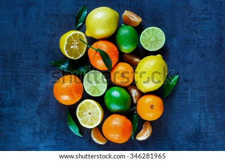 Assorted citrus fruits with leaves on dark vintage background. Agriculture, Gardening, Harvest Concept. Rustic background layout with free text space. Top view. - stock photo