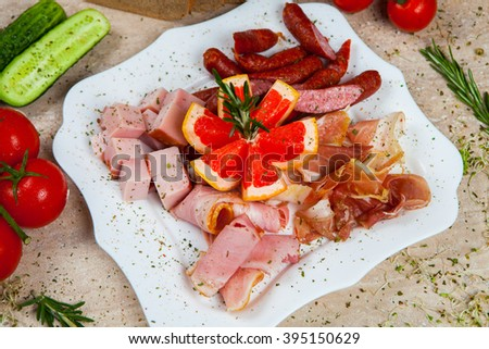 Assorted cold meat platter artistically arranged. Salami, Italian prosciutto. Assorted meat products. A variety of processed cold meat products. Tasty sliced sausage - stock photo