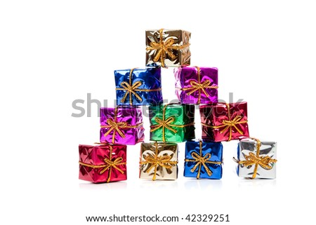 Assorted colored miniature Christmas presents including purple, red, gold, green and blue on  a white background