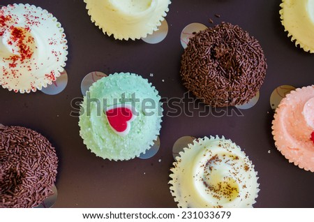 Assorted colorful cup cakes with colorful icing. Top view - stock photo
