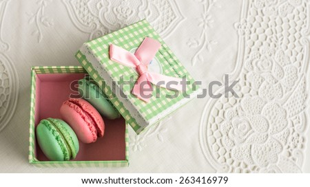 Assorted colorful french macarons in vintage box sweet dessert food  Delicious biscuit merinque from France, small green gift box with pink ribbon for bakery business website blog magazine book cover - stock photo
