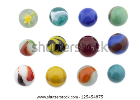 Assorted colorful glass marbles arranged over a white background - stock photo
