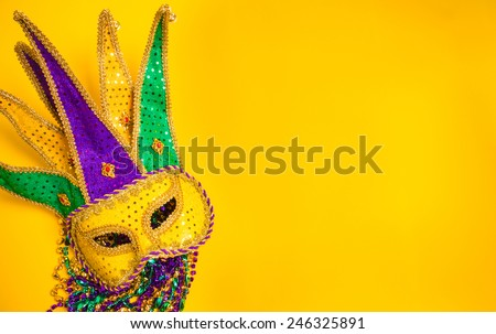Assorted colorful Mardi Gras mask on yellow background with beads - stock photo