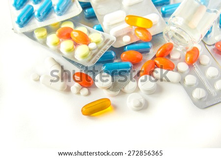 Assorted colorful pills and capsules on white background close up, horizontal, copy space, selective focus, medical concept. - stock photo
