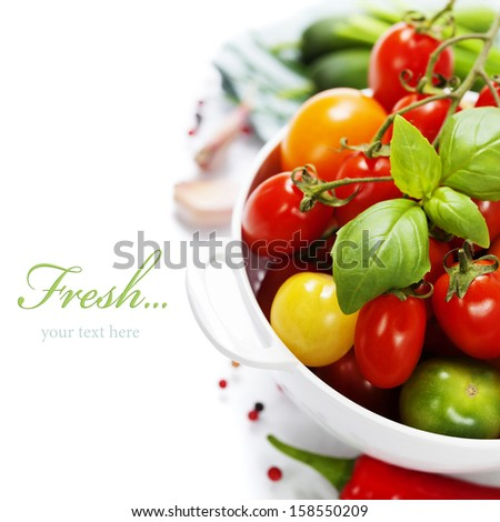 Assorted colorful tomatoes and vegetables in colander on white background - healthy eating concept (with easy removable sample text) - stock photo