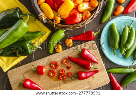Assorted colorful varieties of hot and sweet peppers sitting on table with cutting board, yellowe napkin and blue plate - stock photo