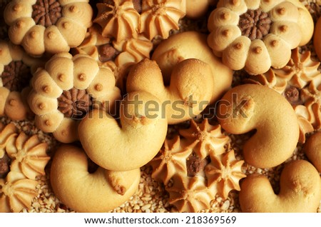 Assorted cookies on chopped hazelnuts, selective focus - stock photo