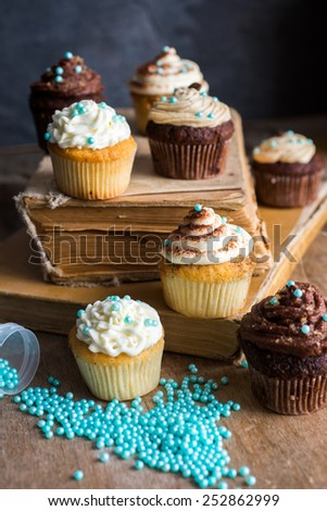 Assorted cupcakes with old books, selective focus - stock photo