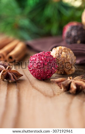 Assorted dark chocolate truffles with dried strawberry pieces and chopped hazelnuts on rustic wooden background, selective focus. Christmas time