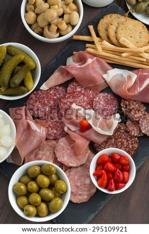 Assorted deli meat snacks, sausages and pickles on a blackboard, top view, vertical - stock photo