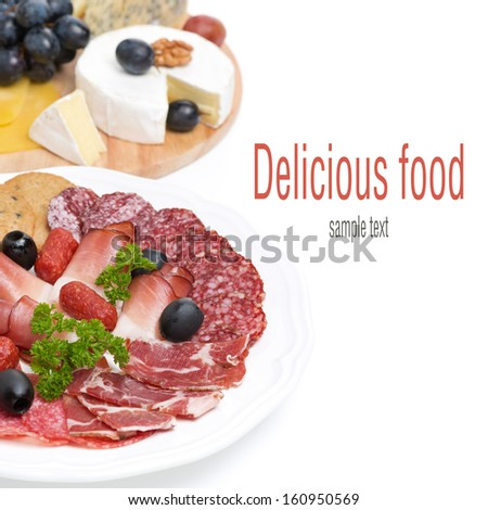 assorted deli meats and a plate of cheese and grapes, isolated on white - stock photo