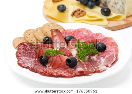 assorted deli meats and a plate of cheese, close-up, isolated - stock photo