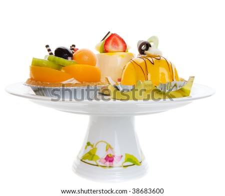 Assorted desserts on a pedestal platter over a white background - stock photo