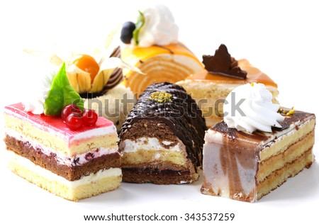 Assorted different mini cakes with cream, chocolate and berries
