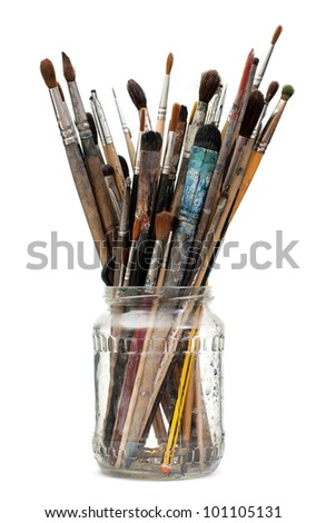 Assorted dirty painting brushes in glass flask - stock photo