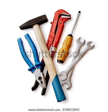 Assorted DIY tools with a red mole grip or adjustable spanner, pliers, screwdriver and pair of spanners, overhead view on white - stock photo